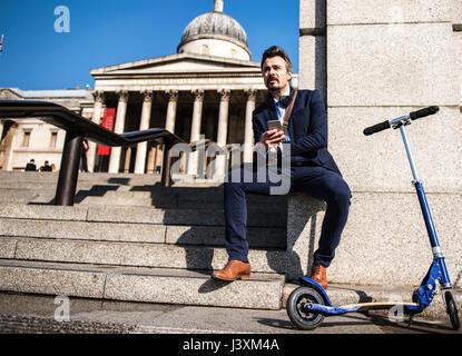 Businessman beside scooter, Trafalgar Square, London, UK - Stock Photo