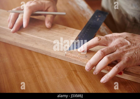 Hands of male carpenter using set square at workbench - Stock Photo