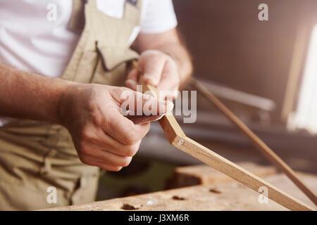 Hands of male carpenter sanding frame at workbench - Stock Photo