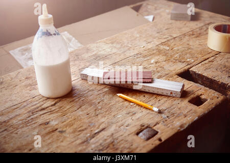 Carpenter's workbench with glue, sandpaper and tape measure - Stock Photo