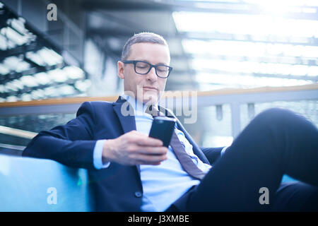 Businessman on sofa looking at smartphone in office atrium - Stock Photo