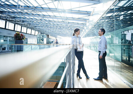 Businessman and woman talking on office balcony - Stock Photo