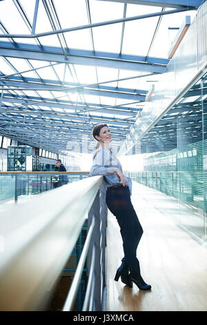 Happy businesswoman leaning against office balcony - Stock Photo