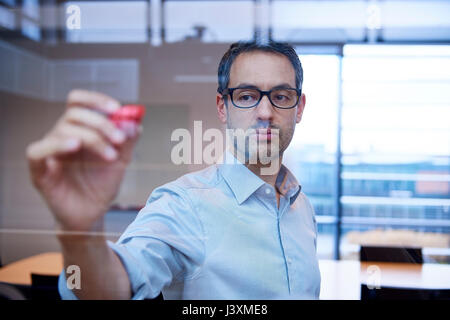 Businessman making presentation drawing graph on office window - Stock Photo