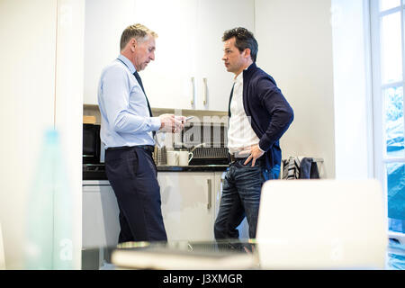 Colleagues in office kitchen having discussion - Stock Photo