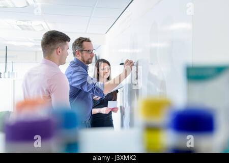 Pharmacists using whiteboard in meeting in pharmaceutical factory - Stock Photo