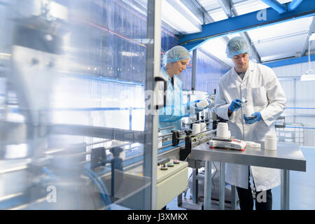Workers on production line in pharmaceutical factory - Stock Photo