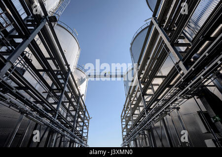 Worker on top of storage tanks in oil blending factory - Stock Photo