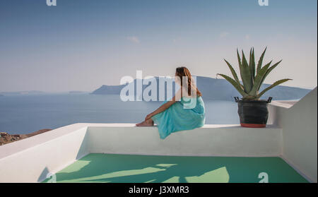 Woman on terrace looking away at view of sea, Santorini, Cyclades, Greece - Stock Photo