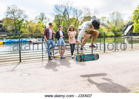 Young male skateboarder doing jump trick for friends in Battersea Park - Stock Photo