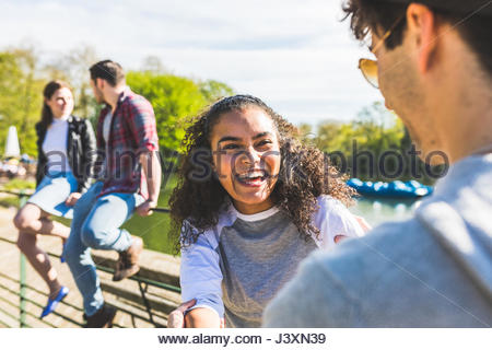 Young couple laughing on lakeside in Battersea Park - Stock Photo