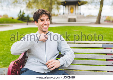 Young man on bench in Battersea Park zipping up hoody - Stock Photo