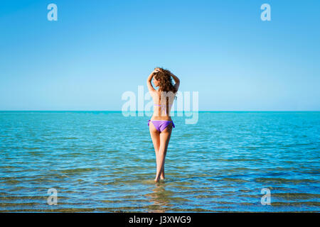 Young beautiful lady with curly hair atanding in water and  looking far against  blue sky background - Stock Photo