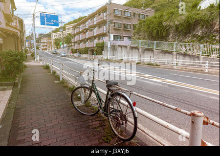Old bicycle parking on a footpath by the street in a city of Japan - Stock Photo