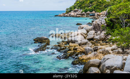 Costline of Koh Tao Islands in Thailand. Granite Rocks and blue clear water hitting Rocks - Stock Photo