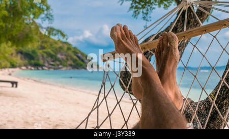 Men feet in Hammock, relaxing on the beach in Haad Rin, Ko Phangan - Stock Photo