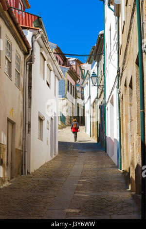 Woman walking Mediterranean, rear view of a solo woman traveler exploring a deserted street in the hill top town - Stock Photo