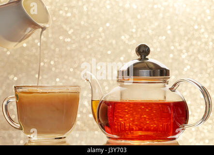 Dissolve milk in a cup of black tea. Transparent teapot and cup on blur background - Stock Photo