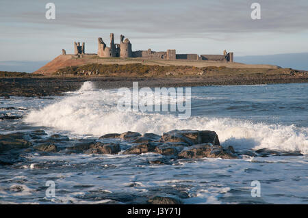 Dunstanburgh Castle on its Whin Sill outcrop, seen from the south. The castle, built in the 14th century, fell into - Stock Photo