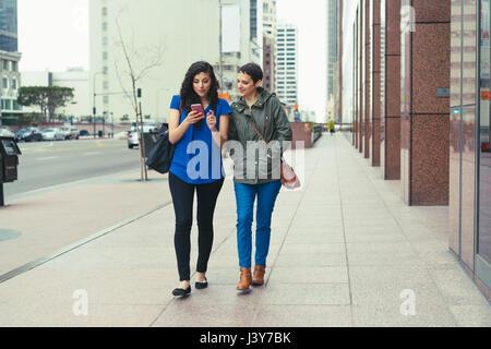 Two female friends walking along street, looking at smartphone