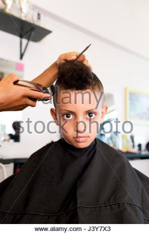 Female barber's hands using hair clippers on boy's hairstyle in barber shop - Stock Photo