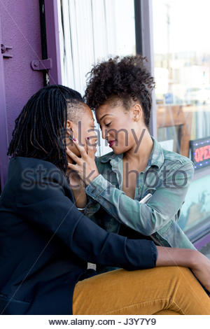 Female barber partners face to face while sitting outside barber shop - Stock Photo