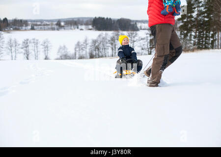 Father pulling son along on sledge, carrying young boy in arms, in snow covered landscape, low section - Stock Photo