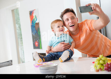 father and toddler son taking selfie in kitchen at home - Stock Photo