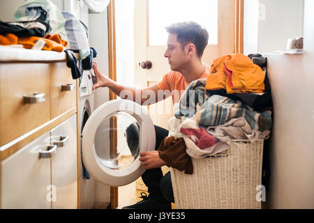 Man doing laundry at home - Stock Photo