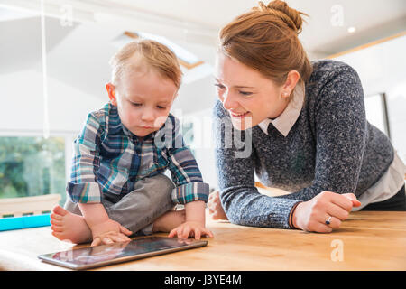 mother and toddler son looking at tablet at home - Stock Photo