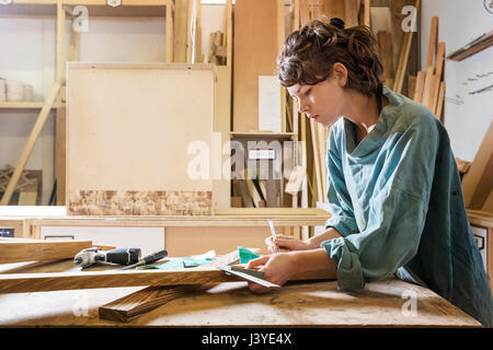Young woman measuring wood in a workshop - Stock Photo