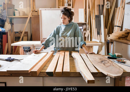 Young woman choosing wood from a selection in a workshop - Stock Photo