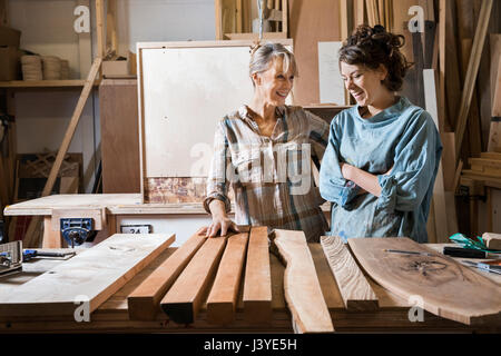 Two women choosing wood from a selection in a workshop - Stock Photo