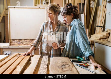 Two women choosing wood from a selection in a workshop, consulting on a tablet - Stock Photo