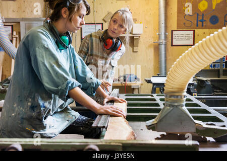 Two women talking and using machinery in a wood workshop - Stock Photo