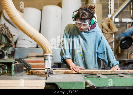 Young woman using machinery in a wood workshop - Stock Photo