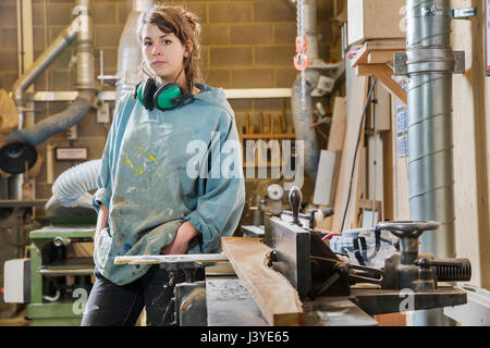 Portrait of young woman next to machinery in wood workshop - Stock Photo