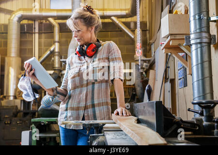 Woman consulting instructions on tablet while using machinery in wood workshop - Stock Photo