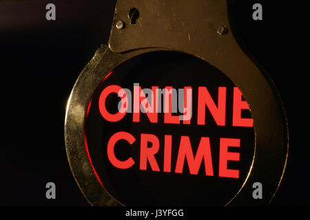Words Online crime on a monitor and handcuffs. - Stock Photo