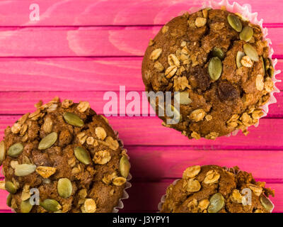 Spiced Carrot Muffin Cakes With Granola and Pumpkin Seeds Against a Pink Background - Stock Photo