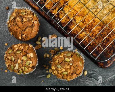 Spiced Carrot Muffin Cakes With Granola and Pumpkin Seeds Against a Black Tile Background - Stock Photo