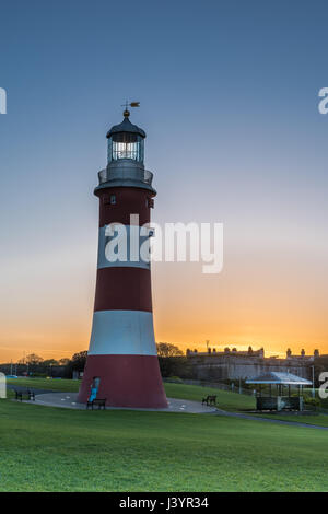 The sun rises behind the iconic Smeatons Tower on Plymouth Hoe in south Devon. - Stock Photo