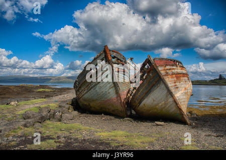 Two old,derelict wooden fishing boats abandoned on Salen beach on the Isle of Mull, Scotland. - Stock Photo