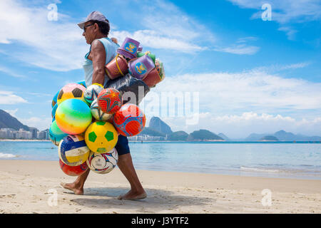RIO DE JANEIRO - FEBRUARY 10, 2017: Brazilian beach vendor walks along Copacabana Beach looking for customers for - Stock Photo