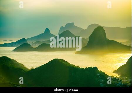 Golden sunset scenic view of the mountainous skyline of Rio de Janeiro, Brazil with Guanabara Bay - Stock Photo