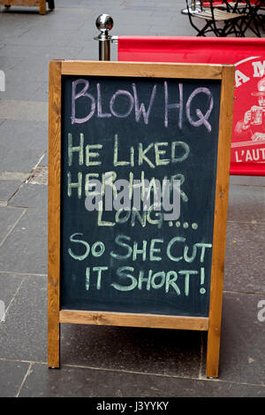 A sign which reads, 'He liked her hair long . . . so she cut it short!', outside a nail bar on Cockburn Street, - Stock Photo