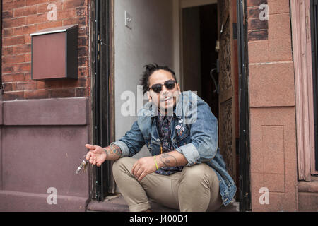 A young man on a doorstep. - Stock Photo