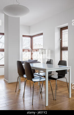 Bright dining room with big windows in modern apartment - Stock Photo