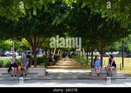 Public seating under oak trees and decorative arches line the promenade at Klyde Warren Park located above a recessed - Stock Photo