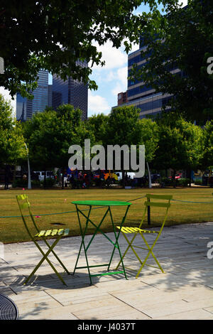 Public tables and chairs line the walkways and tree lined paths around Dallas' downtown Klyde Warren Park built - Stock Photo